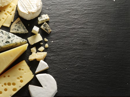 Different types of cheeses on black board.