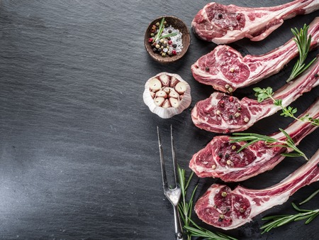 the lamb: Raw lamb chops with garlic and herbs on the old wooden table.