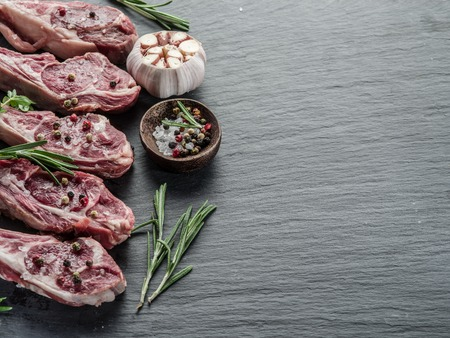 mutton chops: Raw lamb chops with garlic and herbs on the old wooden table.