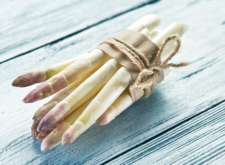 Shoots of white asparagus on the old wooden table.
