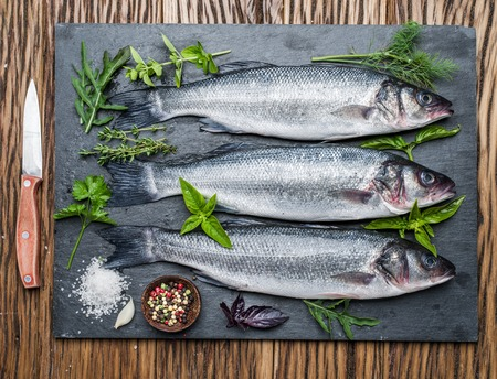 sea bass: Three fish - seabass on a graphite board with spices and herbs.