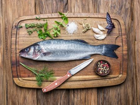 seabass: Fish - lubina en una tabla de madera con especias y hierbas.
