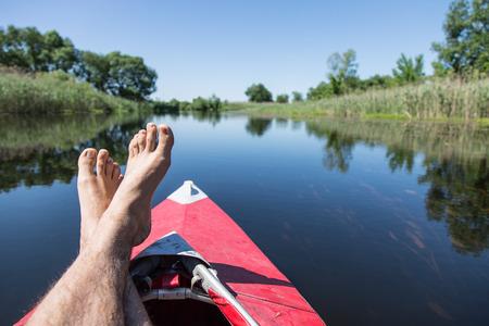 canoe paddle: Mans  feet over canoe.