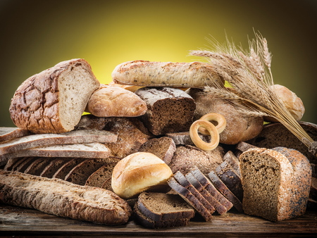 bread: Different types of bread on wooden desk. Stock Photo