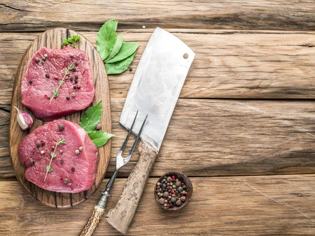cutting board: Raw beaf steaks with spices on a wooden board.