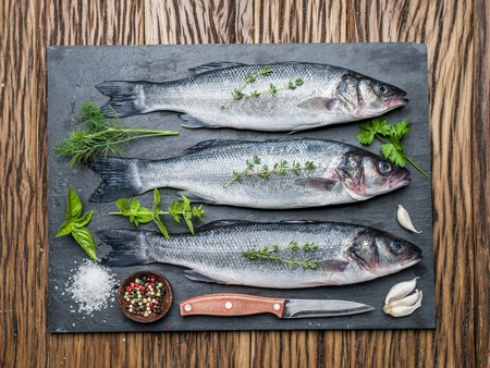 seabass: Three fish - seabass on a graphite board with spices and herbs.