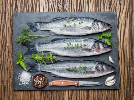 seabass: Tres pescados - lubina en un tablero de grafito con especias y hierbas.