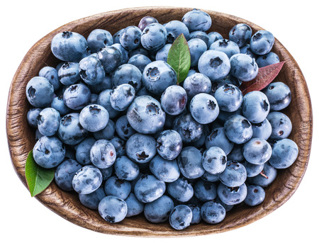 healthy path: Ripe blueberries in the wooden bowl. Top view. File contains clipping paths.
