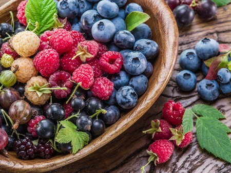 berries: Ripe berries in the wooden bowl on the table. Stock Photo