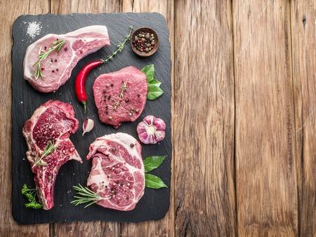 especias: Filetes de carne cruda con especias en la tabla de cortar negro.