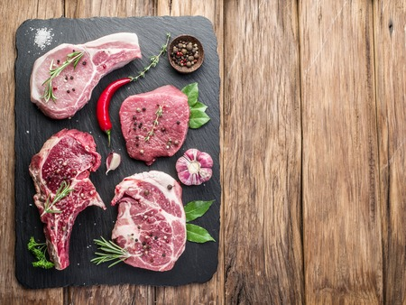 cutting boards: Raw meat steaks with spices on the black cutting board.