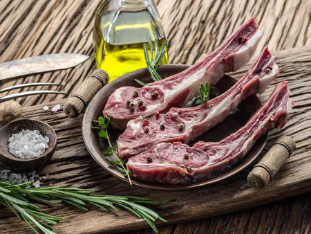 lamb: Raw lamb chops with garlic and herbs on the old wooden table.
