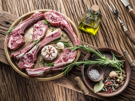 reciept: Raw lamb chops with garlic and herbs on the old wooden table.