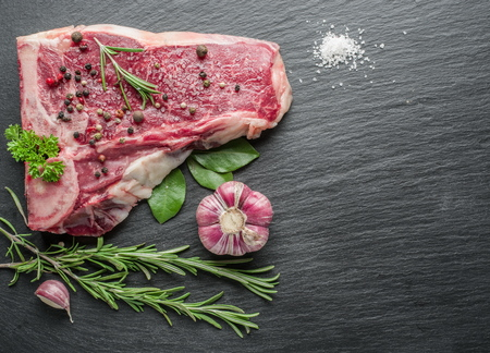 preparation: Raw beef steaks with spices on the black cutting board. Stock Photo