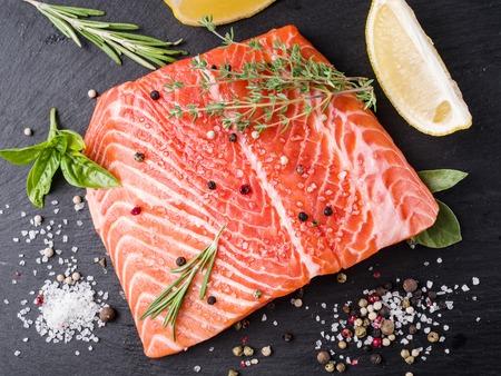 cutting board: Fresh salmon on the black cutting board.