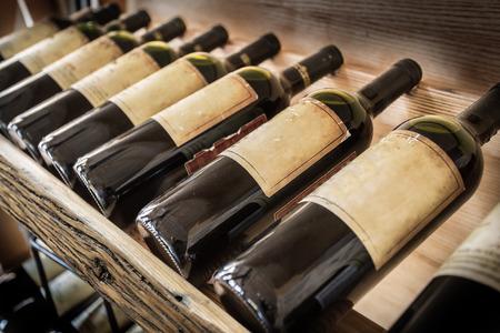 Old wine bottles on the wine shelf. 스톡 콘텐츠