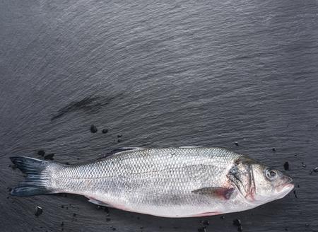 grafit: Surowe ryby seabass na pokładzie grafitu. Zdjęcie Seryjne