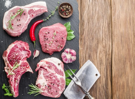 Raw meat steaks with spices on the wooden cutting board. Stock Photo