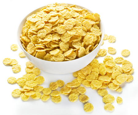 corn meal: Cornflakes cereal in the white bowl. Morning breakfast.