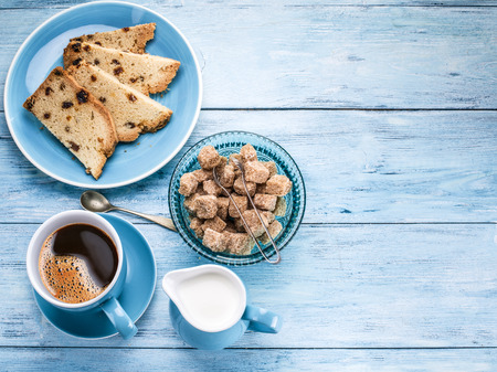 flavour: Cup of coffee, milk jug, cane sugar cubes and fruit-cake on old blu wooden table. Stock Photo