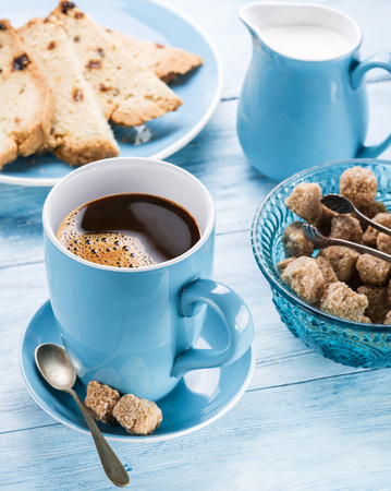 blu: Cup of coffee, milk jug, cane sugar cubes and fruit-cake on old blu wooden table. Stock Photo