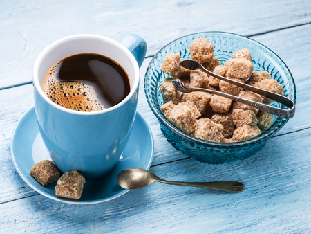 blu: Cup of coffee and cane sugar cubes on old blu wooden table. Stock Photo