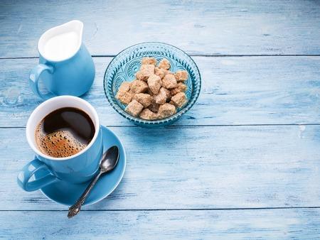 capuchino: Taza de café, jarra de leche y cubos de azúcar de caña en tabla de madera azul.