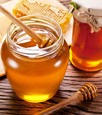 honey jar: Wooden dripper in glass can full of honey on wooden table. Stock Photo