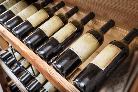 Old wine bottles on the wine shelf. Stok Fotoğraf