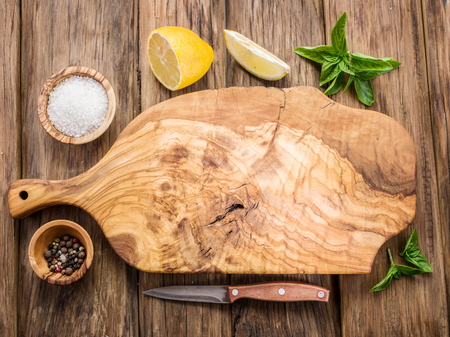 Olive cutting board and spices on a wooden table. Banco de Imagens - 46556655