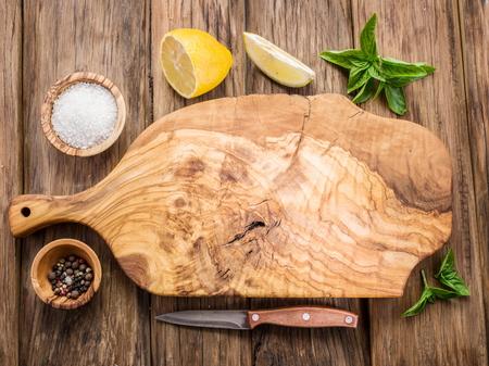 tablero: tabla de cortar de oliva y especias en una mesa de madera. Foto de archivo