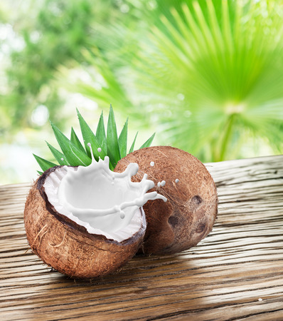 Coconut with milk splash inside it on the wooden table. Stock Photo