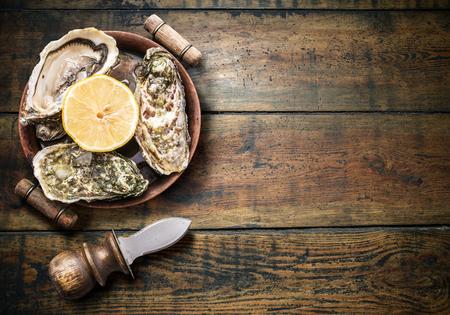 ostra: Las ostras crudas en la mesa de madera vieja.