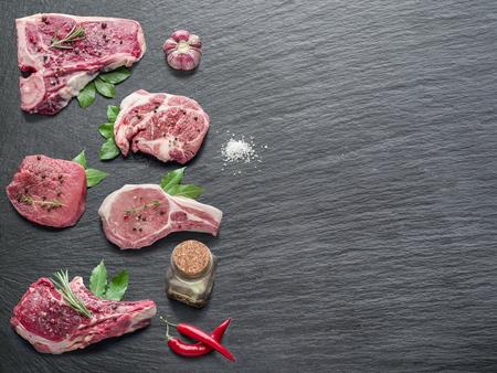 carne cruda: Filetes de carne cruda con especias en la tabla de cortar negro.