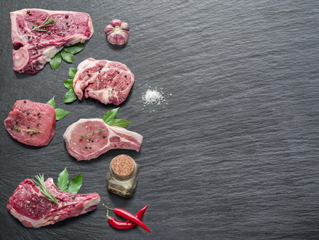 Raw Meat: Raw meat steaks with spices on the black cutting board.