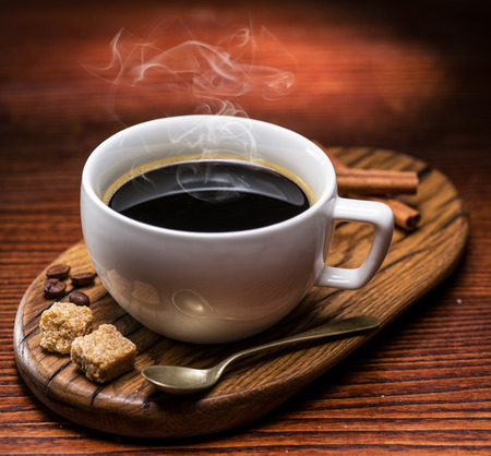 Cup of coffee and cane sugar cubes on wooden table. Stock Photo
