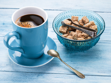 coffee spoon: Cup of coffee and cane sugar cubes on old blu wooden table. Stock Photo