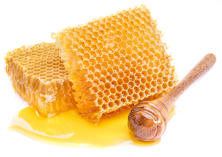 Honeycomb and honey dipper on a white background.  High-quality picture.