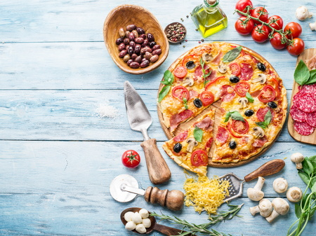 black dish: Pizza with mushrooms, salami and tomatoes. Top view.