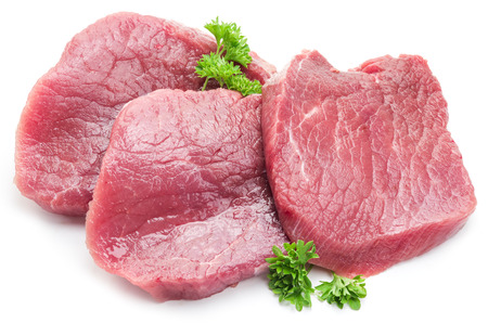 raw: Raw beaf steaks with parsley on a white background. Stock Photo