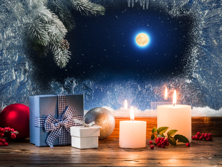 giftwrapped: Christmas presents with burning candle on the windowsill with pattern frost.