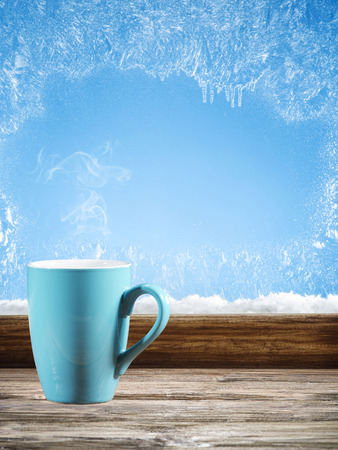 cofee cup: Winter window with blue cofee cup in the day. Frost pattern.
