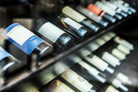 wine cellar: Bottles of wine on the wooden shelf. Stock Photo
