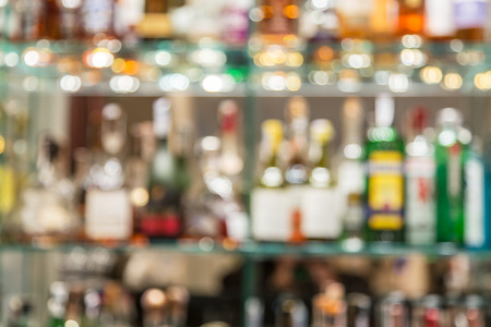 alcohols: Glass bar counter with blurred shelves with alcohol bottles on the background. Stock Photo