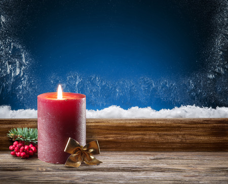 shelf ice: Winter window with burning candle. In the night.