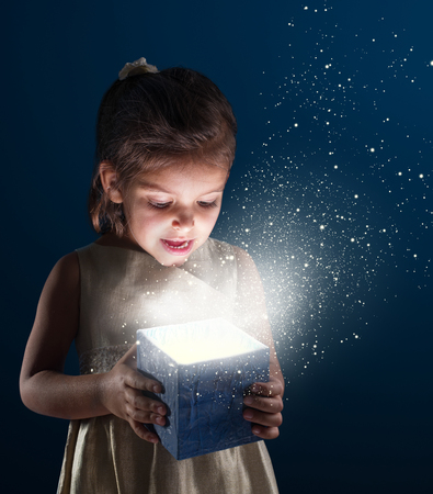 baby open present: Little girl opens a gift. It is lit from within. Dark - blue background.