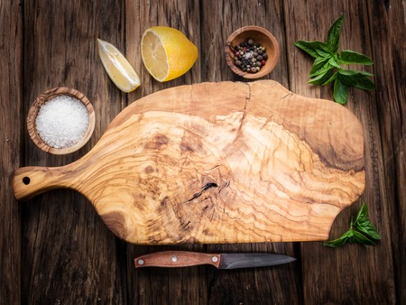 Olive cutting board and spices on a wooden table. Stok Fotoğraf - 49092233