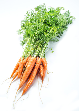 the greens: Carrots with greens on the white background.