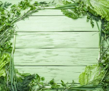 verduras verdes: Hierbas verdes en el fondo verde de madera.