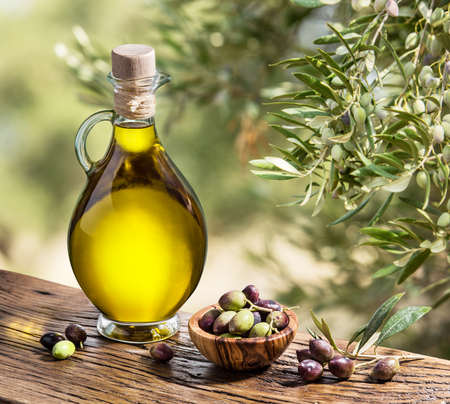 green bottle: Olive oil and berries are on the wooden table under the olive tree.